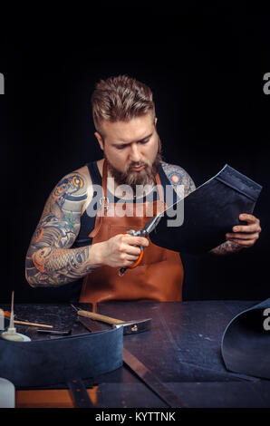 Leather Tanner working with leather using crafting tools in his shop - Stock Photo