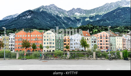 INNSBRUCK, AUSTRIA: Colorful houses on the bank of Inn river; Alps in background - Stock Photo
