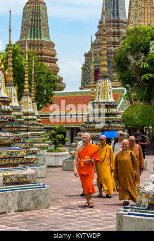 23/06/17 Wat Pho Temple, Bangkok, Thailand. Male and female Monks walk among the Pagodas at the Wat Pho Buddhist - Stock Photo