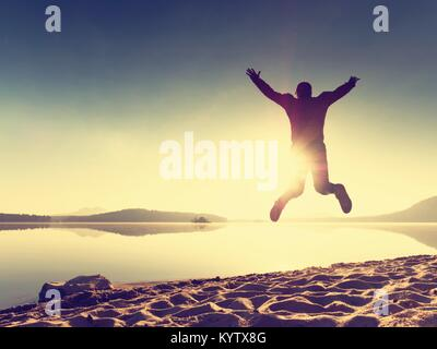 Adult crazy man jumps near water on against red sunset. Empty lake beach - Stock Photo
