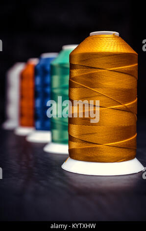 Several of multi-colored spools of threads. Perspective on a black background