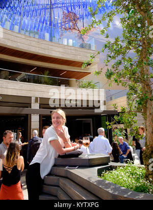 Young Lady smiles over her shoulder as she casually leans on the table that is holding her beer at Broadgate Circle - Stock Photo
