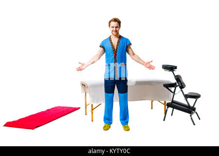 male masseur in blue uniform stands with gesture of greeting hands to the sides with smile next to equipment for - Stock Photo