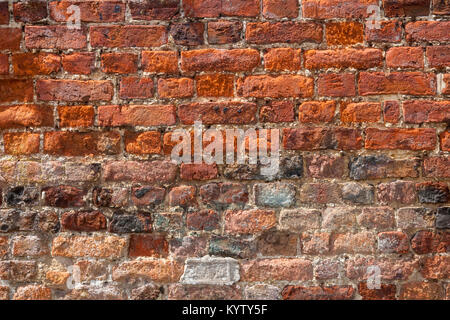 An old weathered, damaged, badly repaired red brick wall full frame - Stock Photo