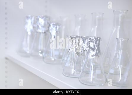 Conical flasks, shelf of clean laboratory glassware on white shelf - Stock Photo