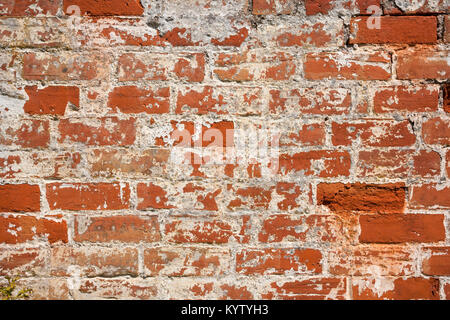 An old weathered, damaged, formerly painted, badly repaired red brick wall full frame background - Stock Photo