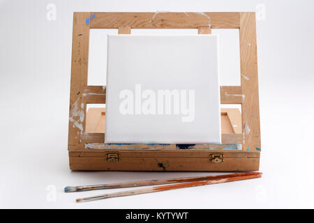 A well used artist's portable easel and case on white seamless with a square blank canvas and two brushes waiting - Stock Photo