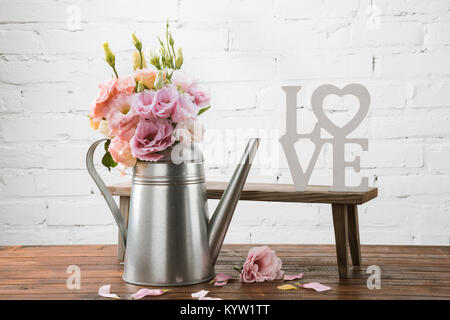 Beautiful blooming flowers in watering can and small bench with love symbol arranged on wooden surface  - Stock Photo