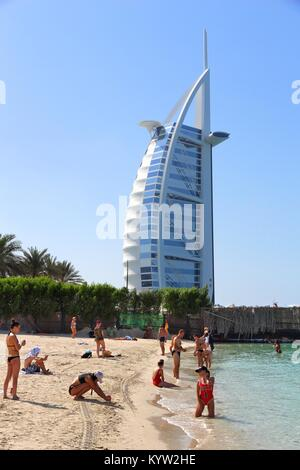 DUBAI, UAE - NOVEMBER 23, 2017: People visit the beach in Dubai, United Arab Emirates. The building in background - Stock Photo