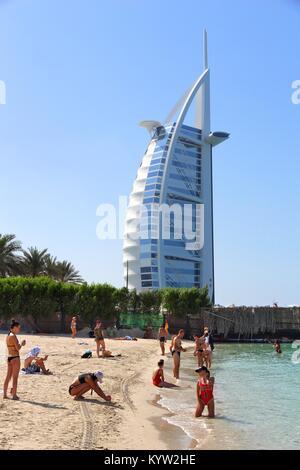DUBAI, UAE - NOVEMBER 23, 2017: People visit the beach in Dubai, United Arab Emirates. The building in background - Stock Photo