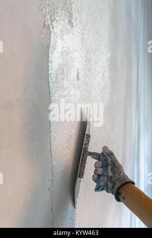 female hand of a plasterer applying fresh white plaster during renovations - Stock Photo