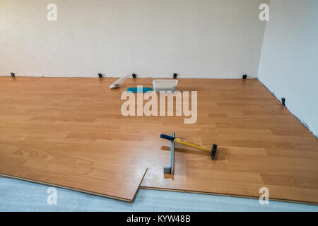 laying wooden flooring during renovation work - Stock Photo