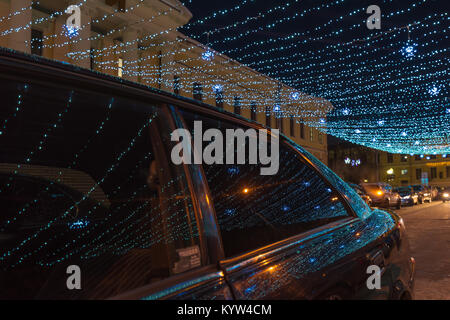 Part of a winter street lit by garlands - Stock Photo