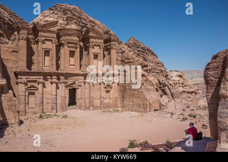 A tourist sitting in the shadow of a rock, observes the Monastery of the city of Petra, in Jordan - Stock Photo