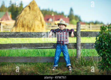 Handsome little boy leaned on wooden fence, straw in mouth. Child as cowboy posing against a wooden fence and smiling. - Stock Photo