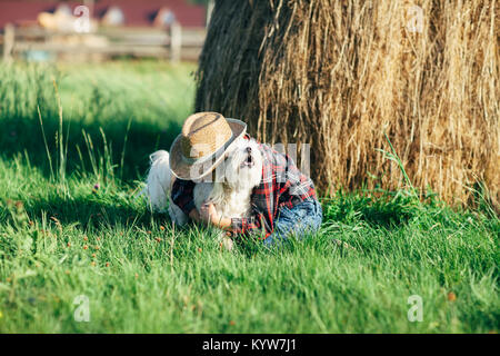 Little boy hugs his dog near haystack in nature. Young man caresses, strokes and scratches the dog behind it ear - Stock Photo