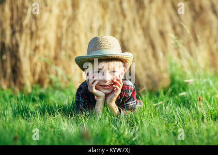 Handsome little boy lies on grass on background of haystack. Child rests in nature, lies on his stomach and propps - Stock Photo