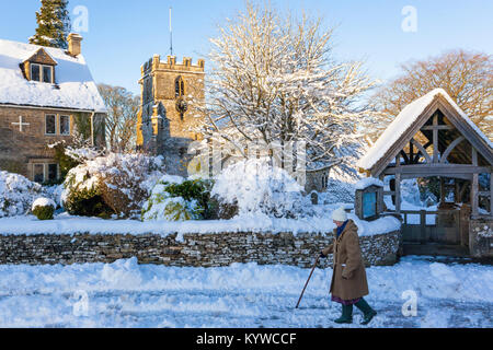 Walking home in the late afternoon on a snowy day past the church of St Andrew in the Cotswold village of Miserden, - Stock Photo