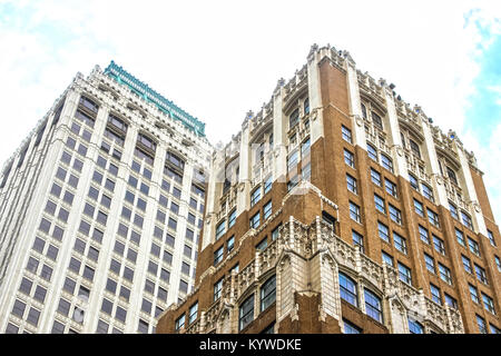 Angled view up at ornate old tall office buildings from street level - Stock Photo