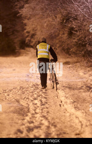 Newtownabbey, Northern, Ireland. 16th Jan, 2018. man walking bicycle home during amber weather warning as heavy - Stock Photo