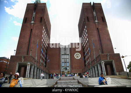 OSLO, NORWAY – AUGUST 18, 2016: Tourists around the main entrance of the Oslo City Hall with fountain of City Hall and clock in Oslo, Norway on August Stock Photo