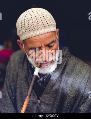 Sonamarg, Jammu & Kashmir - August 11 2017: An Old traditional muslim Kashmiri man smokes Sheesha/Hookah at thajiwas - Stock Photo