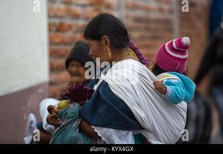 Otavalo, Ecuador - December 30, 2017: indigenous quechua woman carrying child on her back  in the local market - Stock Photo