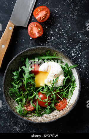 Healthy salad with arugula, tomatoes and poached egg in bowl on dark background. Top view with copy space for text - Stock Photo