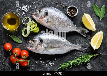 Sea bream or dorado sea fish, olive oil, spices herbs and cooking ingredients on dark slate background. Top view. - Stock Photo