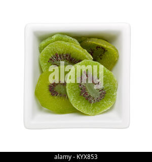 Pieces of candied kiwi fruit in a square bowl isolated on white background - Stock Photo