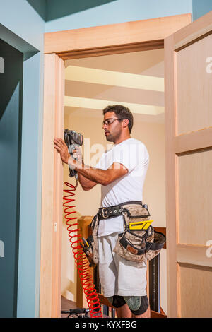 A man finishing the wood framing in a doorway in a newly constructed home. - Stock Photo