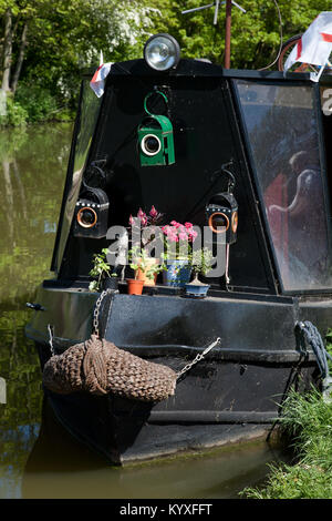 Black narrowboat on Grand Union Canal decorated with old road danger lamps and potted plants. - Stock Photo