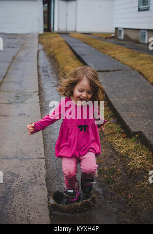 Toddler girl wearing pink, jumping in a mud puddle in a driveway on a rainy day. - Stock Photo
