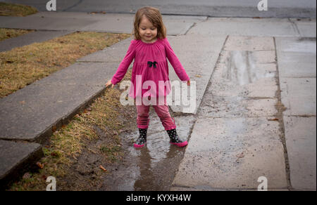 A toddler wearing a pink shirt, pink pants and pink rain boots stands in a mud puddle in a driveway on a rainy day. - Stock Photo