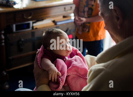A grandfather holds his two month old granddaughter in a pink blanket. - Stock Photo