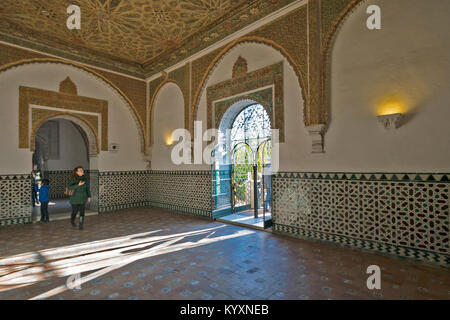 ALCAZAR SEVILLE SPAIN PEOPLE LOOKING AT ISLAMIC ART TILED WALLS AND DECORATED CEILINGS INSIDE A ROOM - Stock Photo