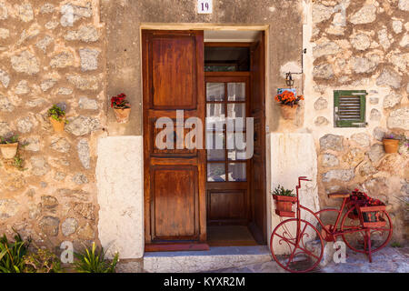 A red bicycle, loaded with flowers, stands in front of an old wooden door in the traditional Spanish medieval city - Stock Photo
