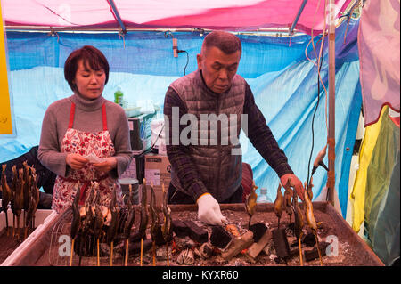 31.12.2017, Tokyo, Japan, Asia - A man prepares freshly roasted fish skewers at a street stall in Tokyo's city district - Stock Photo