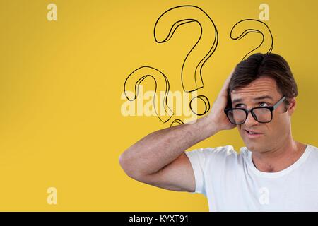Confused man with glasses holding his head on yellow background with question marks - Stock Photo