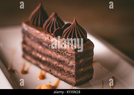 Closeup of a chocolate cake on a white plate on natural light