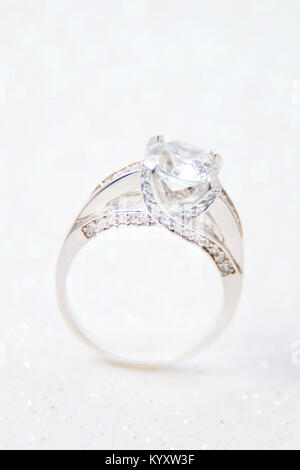 Closeup of a sparkly engagement white gold ring standing on a sparkling background - Stock Photo
