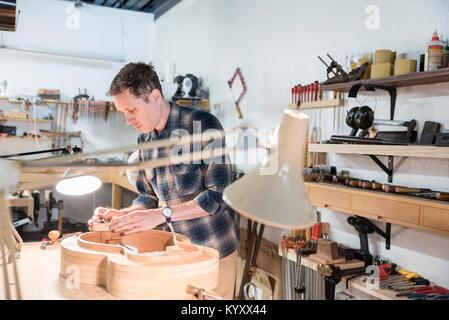 Worker making guitar while standing in workshop - Stock Photo