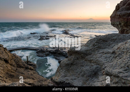 High angle scenic view of waves splashing on rocks against sky with Mt. Fuji in background - Stock Photo