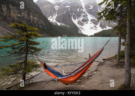 High angle view of hiker resting in hammock by Moraine Lake - Stock Photo