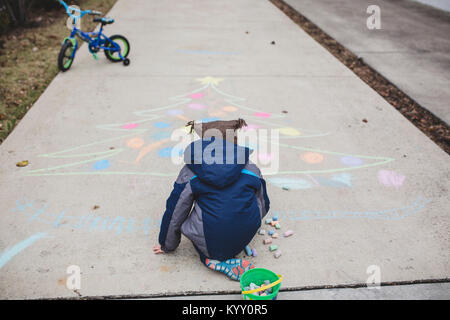 Rear view of boy in warm clothing drawing Christmas tree with chalks on footpath - Stock Photo