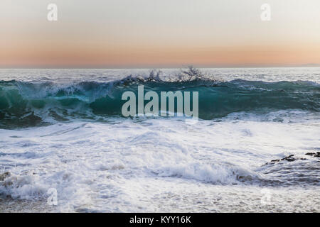 Idyllic view of waves in sea against sky during sunset - Stock Photo