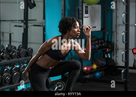Determined woman listening music while exercising in gym - Stock Photo