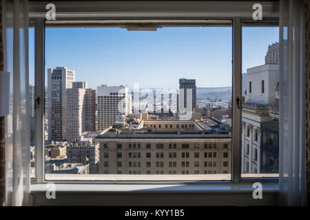 Buildings in city against sky seen through window - Stock Photo