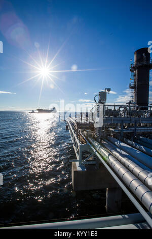 Factory by sea against blue sky during sunny day - Stock Photo