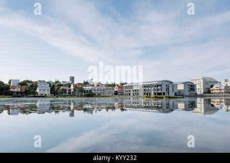 Houses by lake against cloudy sky - Stock Photo